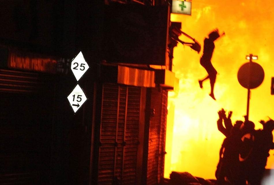 Γυναίκα πηδάει από ένα κτίριο που καίγεται κατά τη διάρκεια των ταραχών του Λονδίνου τον Αύγουστο