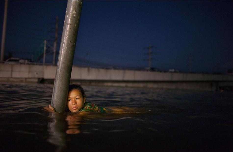 Μια γυναίκα κρατιέται από μια πινακίδα στους πλημμυρισμένους δρόμους στα περίχωρα της Μπανγκόκ στις 24 Οκτωβρίου.