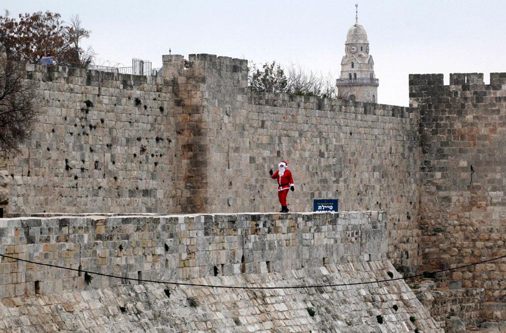 Ένας Παλαιστίνιος άνδρας ντυμένος Αη Βασίλης περπατά σε τείχη της παλιάς πόλης της Ιερουσαλήμ