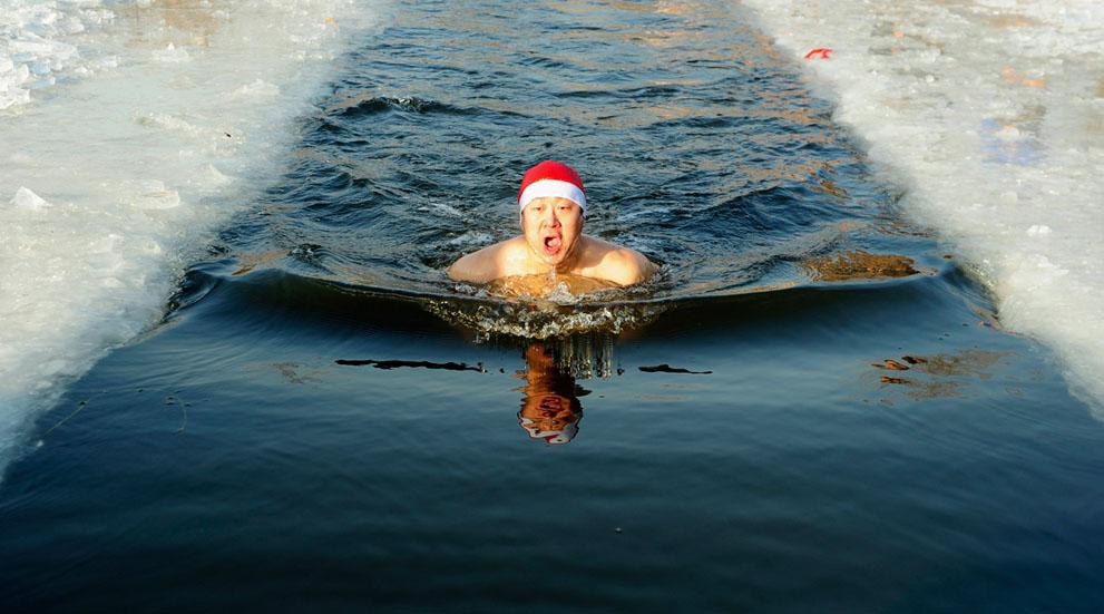 Ένας κολυμβητής φοράει Αϊ Βασιλιάτικο καπέλο και κολυμπά στο παγωμένο νερό στην Shenyang, Liaoning επαρχία, της Κίνας