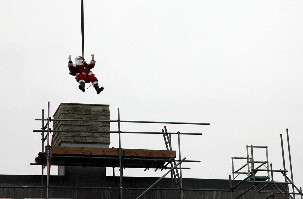 Ένας άντρας ντυμένος Άγιος Βασίλης ανυψώνεται με γερανό στο Somerford Keynes της Αγγλίας,σε μια ειδική διαμορφωμένη καμινάδα  για να χωρέσει τον Άγιο Βασίλη
