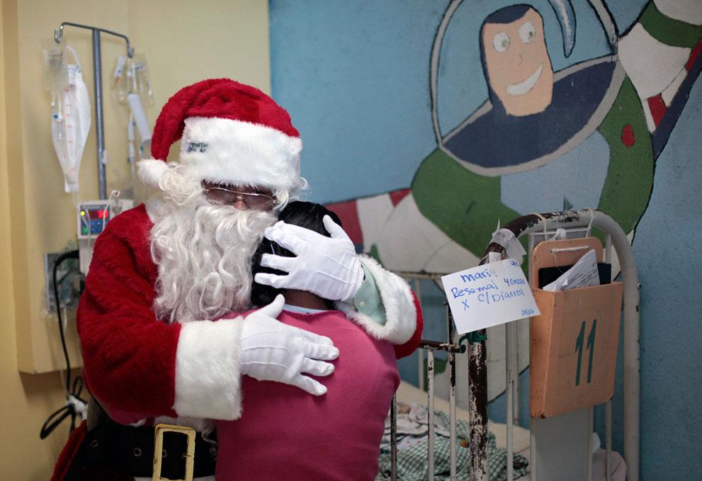 Άγιος Βασίλης αγκαλιάζει μια γυναίκα κατά τη διάρκεια μιας εκδήλωσης στο Νοσοκομείο San Juan de Dios , στην πόλη της Γουατεμάλας,