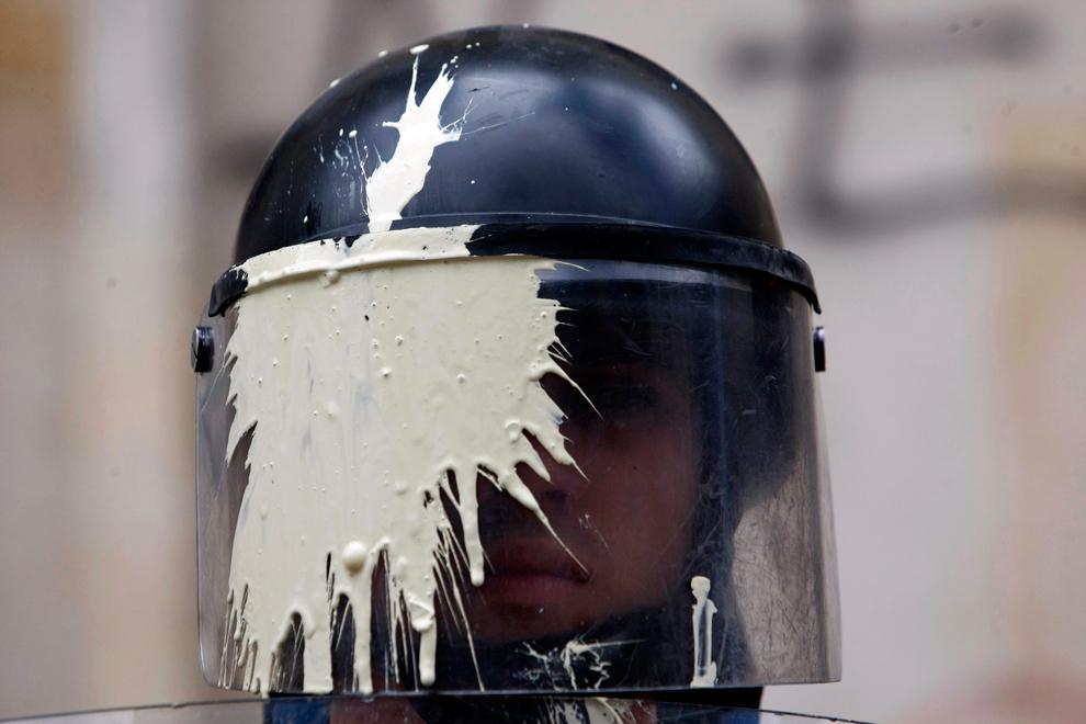Αστυνομικός ΜΑΤ με τη μάσκα του βαμμένη από μπογιά που του ριξανε  μαθητές παρακολουθεί την πορεία από τους εκπαιδευτικούς και τους μαθητές που διαμαρτύρονται για θέματα που αφορούν τις εκπαιδευτικές πολιτικές της κυβέρνησης στην Μπογκοτά, Κολομβία