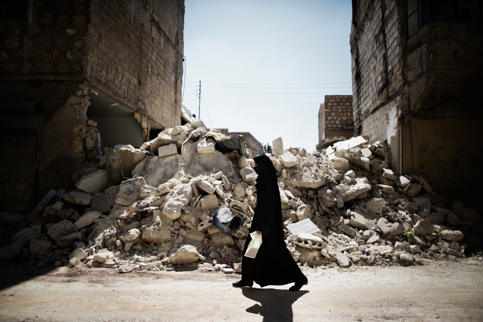 Μια γυναίκα περπατά δίπλα από ένα κατεστραμμένο κτίριο στη Συρία