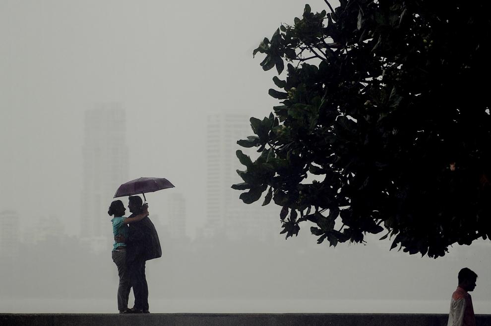 Ζευγάρι Ινδών βρίσκει καταφύγιο κάτω από μια ομπρέλα κατά τη διάρκεια της βροχή στη Βομβάη . Οι βροχές των μουσώνων, το κλειδί για την οικονομία της Ινδίας, ξεκίνησαν α στις 11 Ιουλίου, αλλά είναι  23%  κάτω του μέσου όρου, σύμφωνα με αξιωματούχους