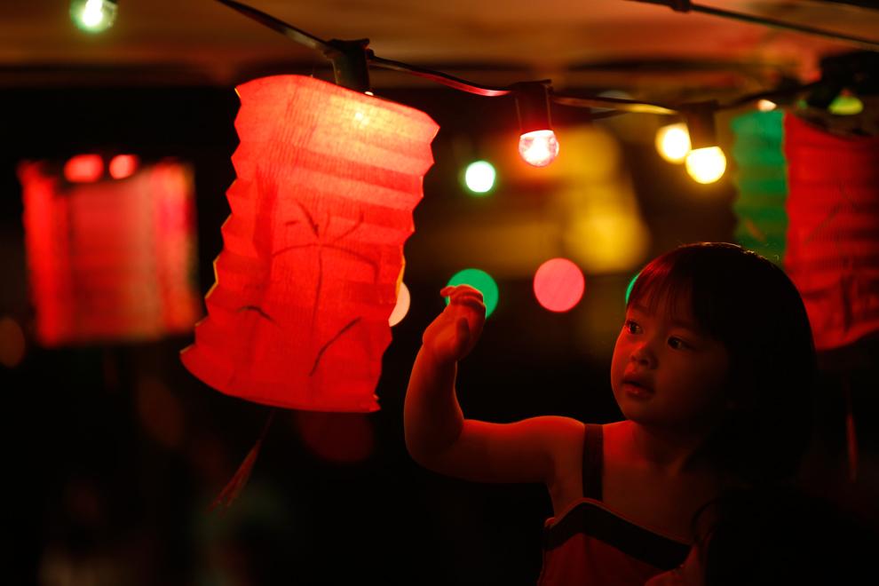Κορίτσι αγγίζει ένα φανάρι σε υπαίθριο εστιατόριο κατά τη διάρκεια του κινεζικου φεστιβάλ  στα μέσα του φθινοπώρου στο Χονγκ Κονγκ