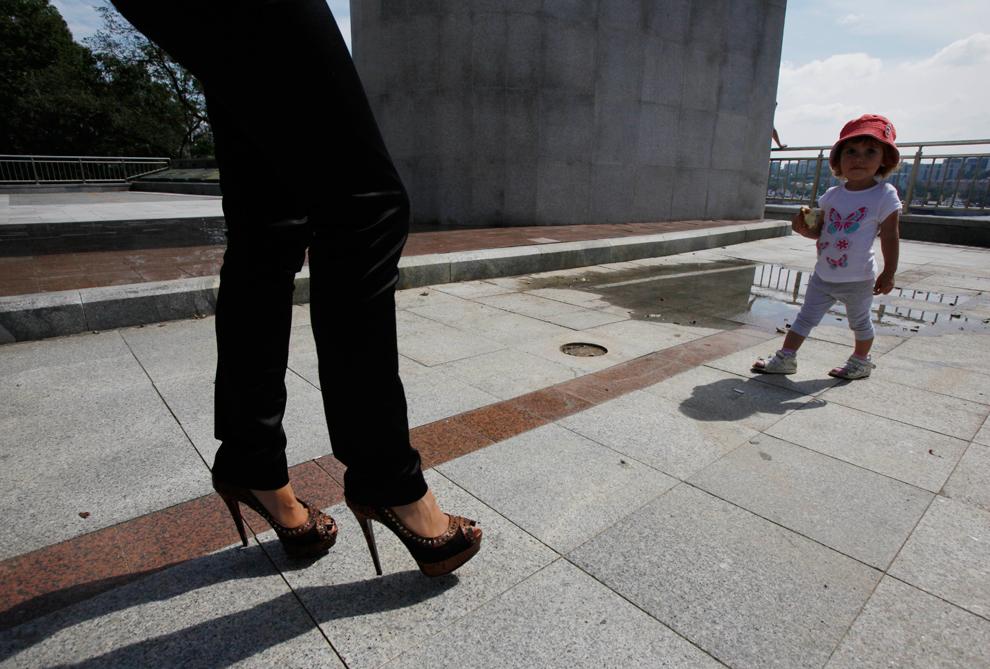 Μια γυναίκα παίρνει το παιδί της για μια βόλτα κοντά σε ένα μνημείο στο Βλαδιβοστόκ, Ρωσία