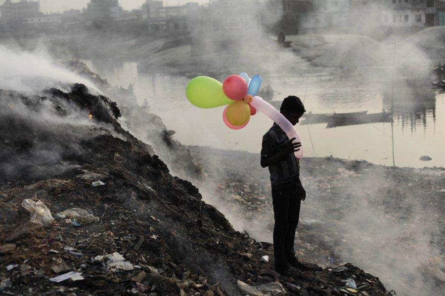 Ένα αγόρι δίπλα σ' ένα ποτάμι στην πρωτεύουσα του Μπαγκλαντές, ενώ αναδύεται καπνός  από μία χωματερή.
