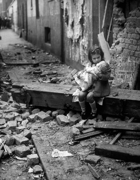 Κοριτσάκι καθησυχάζει την κούκλα του στα ερείπια του βομβαρδισμένου σπιτιού της, Λονδίνο, 1940.