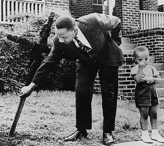 Ο Μάρτιν Λούθερ Κινγκ και ο γιος του, απομακρύνοντας καμένο σταυρό από την μπροστινή αυλή τους, 1960.