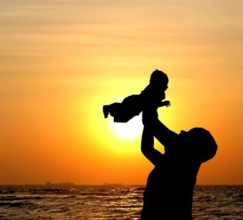 Ευτυχισμένος γονιός με το παιδί του στο ηλιοβασίλεμα