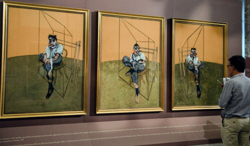 "A journalist looks at Francis Bacon's paintings "" Three Studies of Lucian Freud - 1969 "" during the opening of the exhibition 'Caravaggio and Bacon' at the Borghese museum"