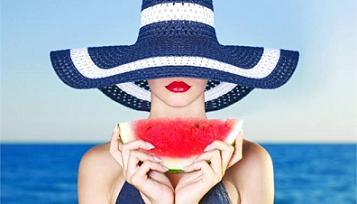 Γυναίκα απολαμβάνει καρπούζι με φόντο τη θάλασσα.
