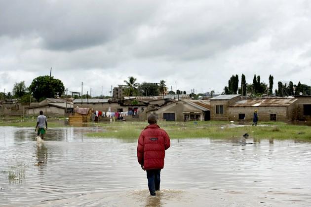 Ένας άντρας προσπαθεί να φτάσει στο σπίτι του περνώντας μέσα από ένα πλημμυρισμένο χωράφι στην περιοχή Mikocheni του Dar es Salaam, Τανζανία, στις 12 Απριλίου