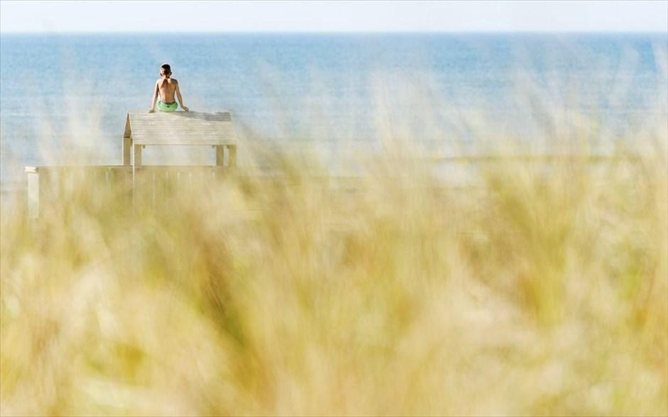 Ένα αγόρι απολαμβάνει τη θέα της θάλασσας στην παραλία Katwijk aan Zee της Ολλανδίας.