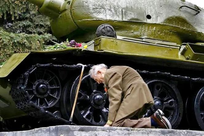 Ένας Ρώσος βετεράνος πολέμου γονατίζει δίπλα από το τανκ που χρησιμοποιούσε στον πόλεμο, το οποίο τώρα είναι παροπλισμένο και χρησιμοποιείται ως μνημείο.