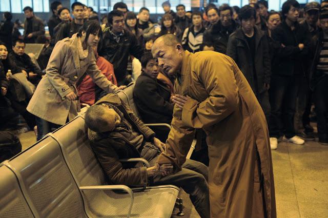 Ένας άγνωστος μοναχός προσεύχεται για έναν ηλικιωμένο που πέθανε ξαφνικά, ενώ περίμενε το τρένο, Κίνα.