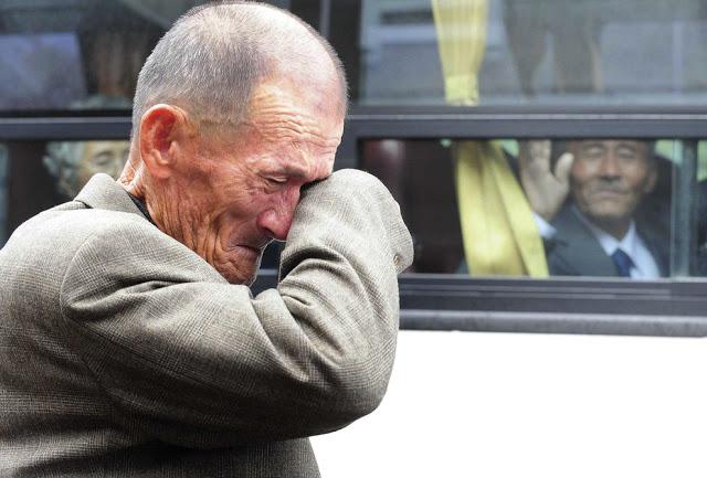 Στο φόντο ένας Βορειοκορεάτης χαιρετάει έναν Νοτιοκορεάτη συγγενή του, ο οποίος σκουπίζει τα δάκρυα του. Σε 436 Νοτιοκορεάτες επιτράπηκε να περάσουν 3 μέρες στην Βόρεια Κορέα για να συναντήσουν 97 συγγενείς τους. Οι δύο χώρες τους κρατούσαν χωριστά από τον πόλεμο του 1950-1953.