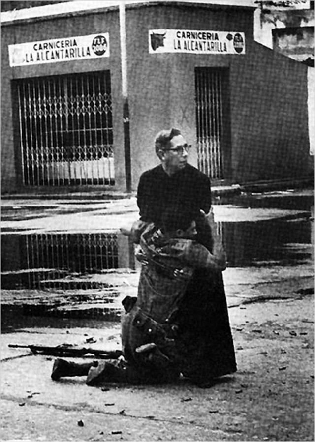 Ένας στρατιώτης πέφτει στα γόνατα μετά από χτύπημα ελεύθερου σκοπευτή στην Βενεζουέλα ενώ ο εφημέριος του Ναυτικού του δίνει τις τελευταίες ευχές.