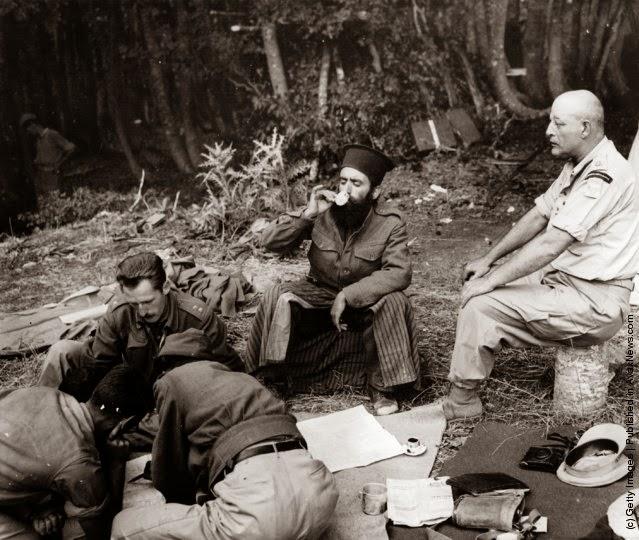 Αξιωματικοί σχεδιάζουν επίθεση, ενώ ένας παπάς πίνει καφέ. Κάθε ταξιαρχία είχε κι έναν παπά που ταξίδευε μαζί τους.  (Φωτογραφία από τον Federico Patellani / Getty Images). 1947