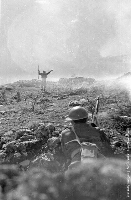 Ένας εξαντλημένος αντάρτης παραδίνεται στον ελληνικό στρατό κατά τη διάρκεια του Ελληνικού Εμφυλίου Πολέμου. (Φωτογραφία από Bert Hardy / Getty Images). 1948