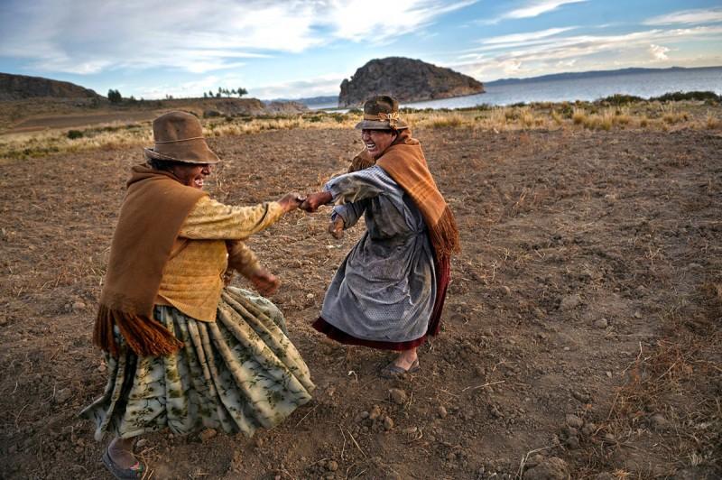 Η 70χρονη Ντομίνκα Ολάρι (αριστερά) και η 70χρονη Μανουέλα Αβίλε (δεξιά) χορεύουν μετά από τον θερισμό της πατάτας. Η Αβίλε έχει την Γη και η Ολάρι δουλεύει και παίρνει ως αντάλλαγμα φαγητό, στην Βολιβία.