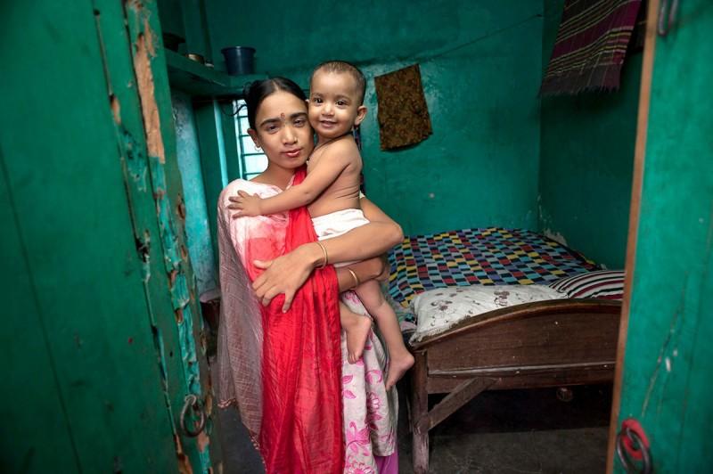 Η 27χρονη Λαμπόνε αγκαλιάζει την ενός έτους κόρη της λίγο πριν πάει στην δουλειά της, στο Μπανγκλαντές.