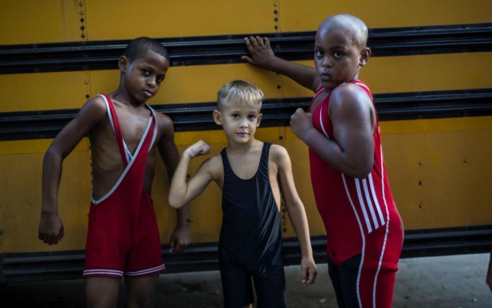Τα άγουρα ποντίκια τους επιδεικνύουν οι επίδοξοι αθλητές της πάλης, Braimond (αριστερά), Raimel και Junior. Μαζί με μια ντουζίνα ακόμη συνομήλικούς τους προπονούνται σε ένα πάρκο στην παλαιά Αβάνα. Σκοπός τους; Να μοιάσουν στον διάσημο Mijain Lopez. Τον Κουβανό αθλητή που κέρδισε δυο χρυσά μετάλλια σε Ολυμπιακούς αγώνες και πέντε παγκόσμια πρωταθλήματα στην ελληνορωμαϊκή πάλη, κάνοντάς τον έναν από τους πιο διάσημους αθλητές στην Κούβα. (AP Photo/Ramon Espinosa)