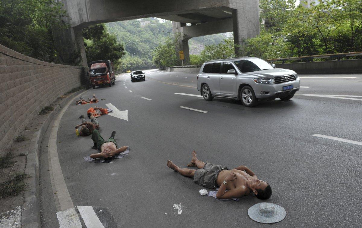 Eργάτες που δουλεύουν σε κοντινή απόσταση παίρνουν έναν υπνάκο πάνω στο δρόμο, ενώ τ αυτοκίνητα περνούν δίπλα τους. Τοποθεσία Δήμος Chongqing. 23 Ιουλίου, 2013
