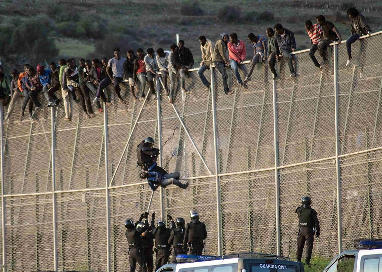 Ισπανός αστυνομικός τραβά ένα αφρικανικό μετανάστη από φράχτη στα σύνορα μεταξύ Μαρόκου και Ισπανίας.Περίπου 300 μετανάστες επιχείρησαν να περάσουν τα σύνορα προς την Ισπανία αλλά λίγοι κατάφεραν να περάσουν το φράχτη.