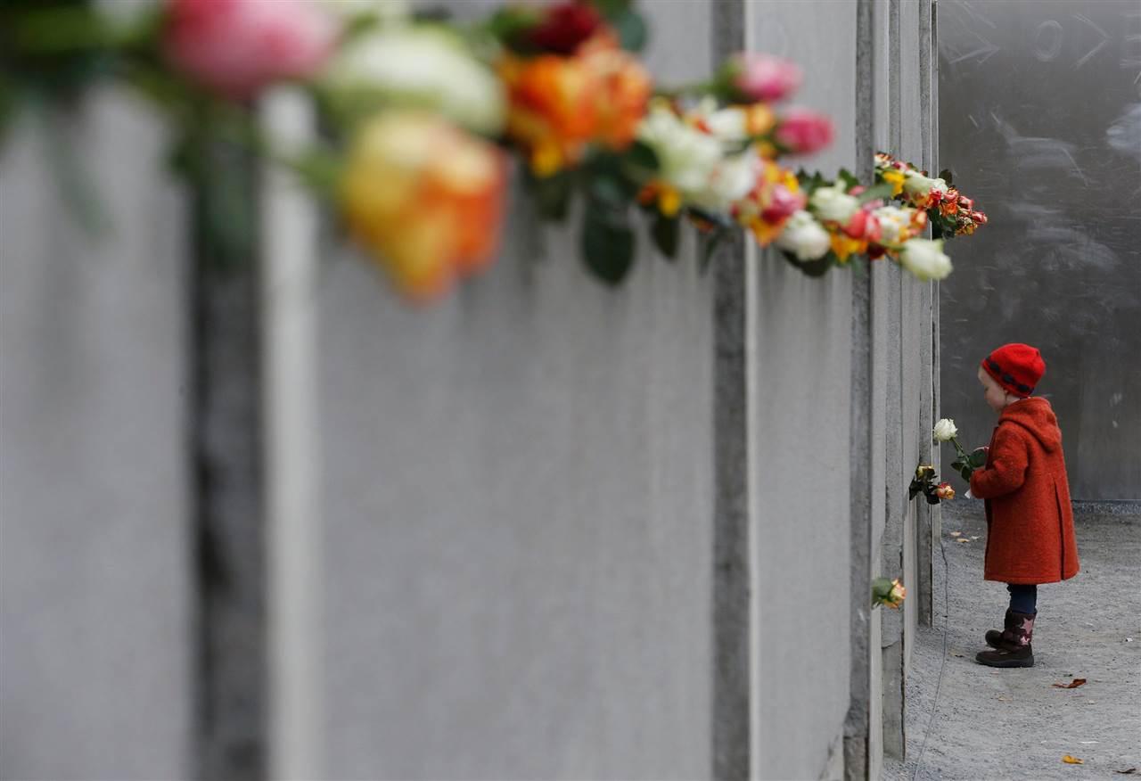 Νεαρή κοπέλα αφήνει ένα τριαντάφυλλο στο μνημείο του Τείχους του Βερολίνου στην Bernauer Strasse, κατά τη διάρκεια της τελετής για την 25η επέτειο από την πτώση του Τείχους του Βερολίνου, στις 9 Νοεμβρίου.