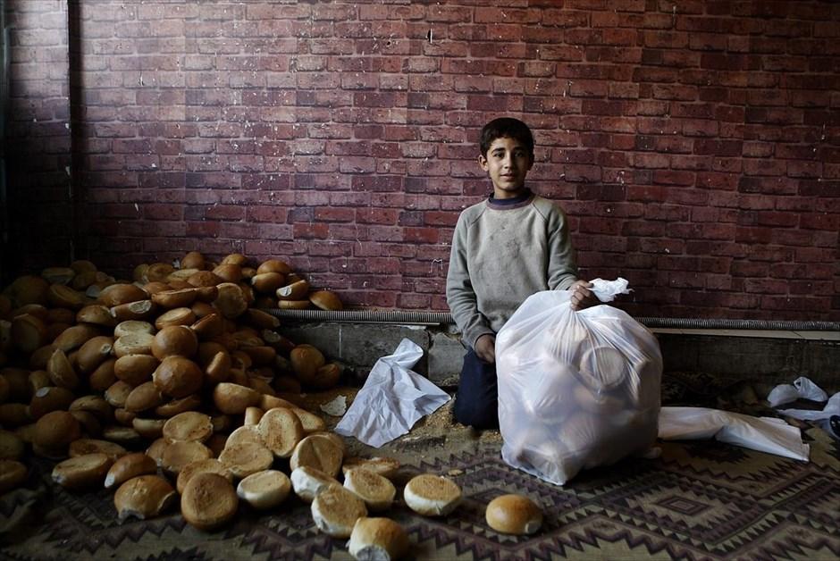Ο δεκατριάχρονος Κελάλ Ίσο φωτογραφίζεται στον φούρνο όπου εργάζεται 7 - 12 ώρες την ημέρα, με εβδομαδιαίο μισθό 20 τουρκικές λίρες (7 ευρώ) στο Σουρούτς. Ο Κελάλ ζει με την οικογένειά του σε αποθήκη. Ο πατέρας του δούλευε σε οικοδομές αλλά είναι πλέον άνεργος. Αρμοδιότητα του Κελάλ είναι ο καθαρισμός του καταστήματος και η συσκευασία του ψωμιού.