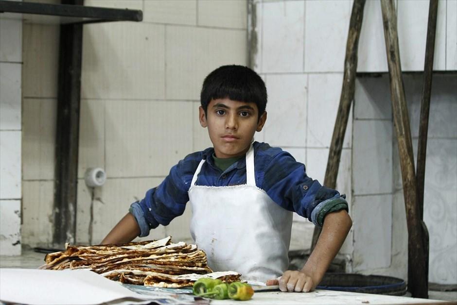 Ο δεκατετράχρονος Φερζάντ Χαμπέσι φωτογραφίζεται σε παραδοσιακό εστιατόριο που ειδικεύεται στα λαχματζούν στο Σουρούτς. Ο Φερζάντ πληρώνεται 5 τουρκικές λίρες (1,7 ευρώ) την εβδομάδα. Η οικογένειά του αναγκάστηκε να εγκαταλείψει το μανάβικο που διατηρούσε στο Κομπάνι, μετά την έναρξη των εχθροπραξιών και τώρα φιλοξενείται από συγγενείς στην Τουρκία. Όνειρο του Φερζάντ είναι να επιστρέψει στο σχολείο του στη Συρία.
