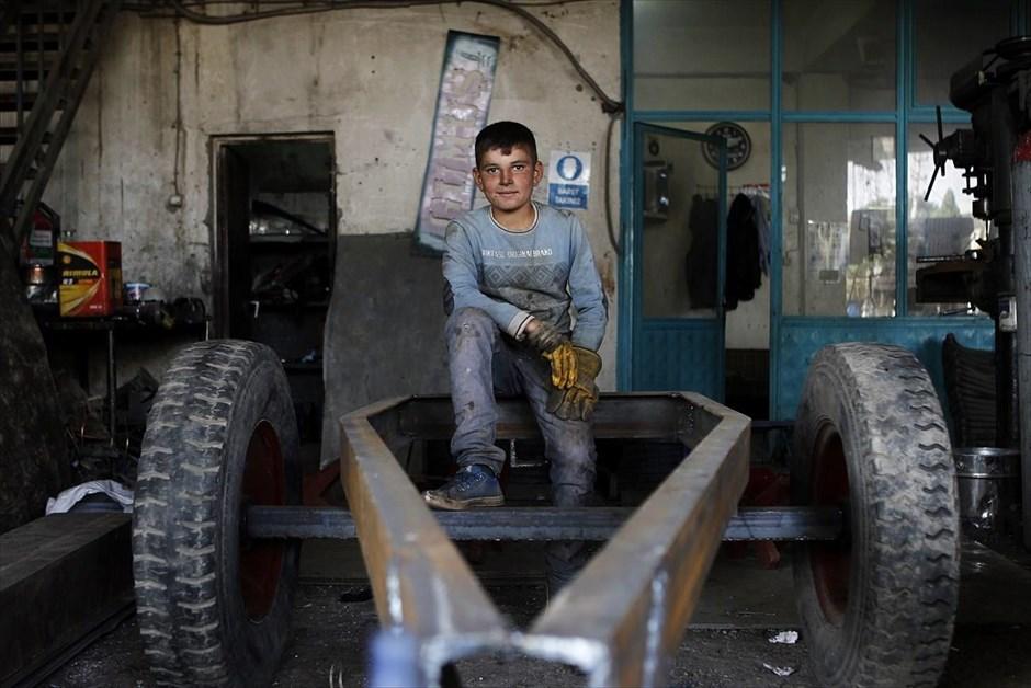 Ο δωδεκάχρονος Αζίζ Καντίρ φωτογραφίζεται στο συνεργείο επισκευής αγροτικών μηχανημάτων, όπου εργάζεται με τον πατέρα του, στο Σουρούτς. Ο εβδομαδιαίος μισθός του είναι 20 τουρκικές λίρες (7 ευρώ) περίπου. Ζούσε με την οικογένειά του στην περιοχή Μιναζάρα, κοντά στο Κομπάνι, και τώρα μένει με συγγενείς στο Σουρούτς. Ο αδερφός του αποφάσισε να φύγει για τον Λίβανο, όπου έχει βρει εργασία.