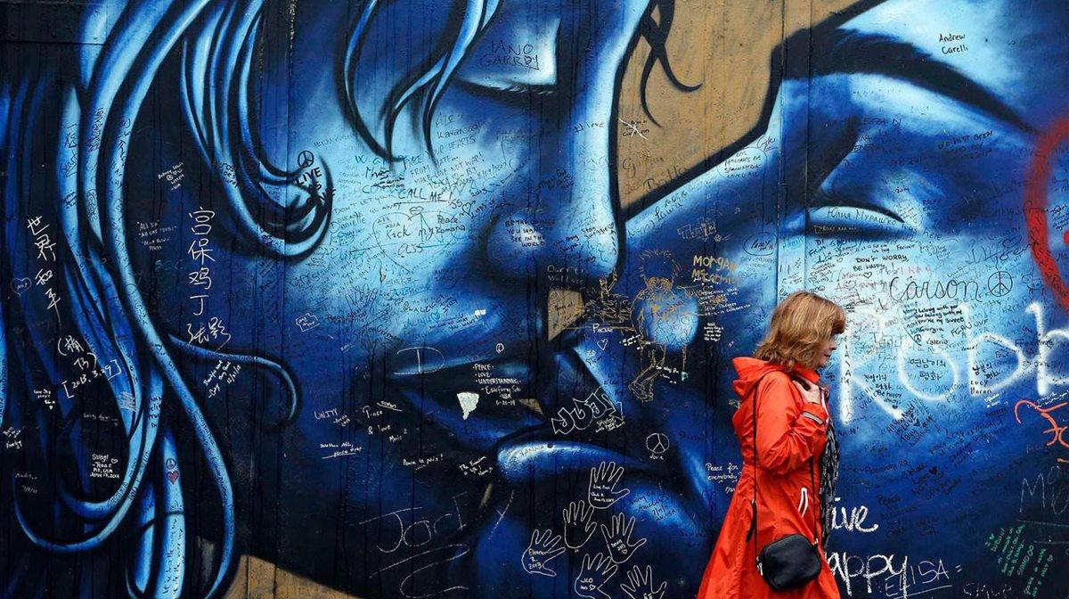 Μια τουρίστρια περπατά κατά μήκος του τοίχου της Ειρήνης στο Δυτικό Μπέλφαστ.
