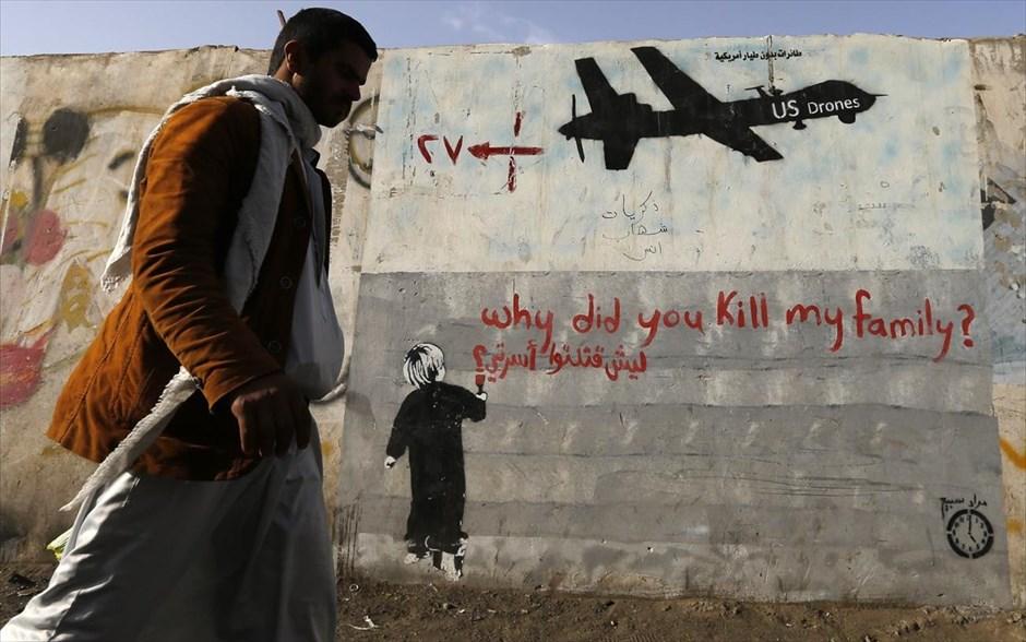 Άνδρας στην Σαναά περπατάει μπρόστα από γκράφιτι που καταγγέλει τα χτυπήματα  από αμερικανικά drones. Oι αρχές της Υεμένης πλήρωσαν αποζημιώσεις δεκάδες χιλιάδες δολαρίων στα θύματα των drones με χρήματα που έδωσαν γι' αυτό το λόγο οι ΗΠΑ.