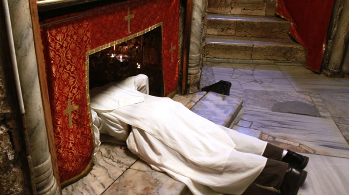 Προσκυνητής προσεύχεται στο Σπήλαιο του Ναού της Γεννήσεως στη Βηθλεέμ και ο φωτογραφικός φακός τον συνέλαβε σε στιγμή κατάνυξης.