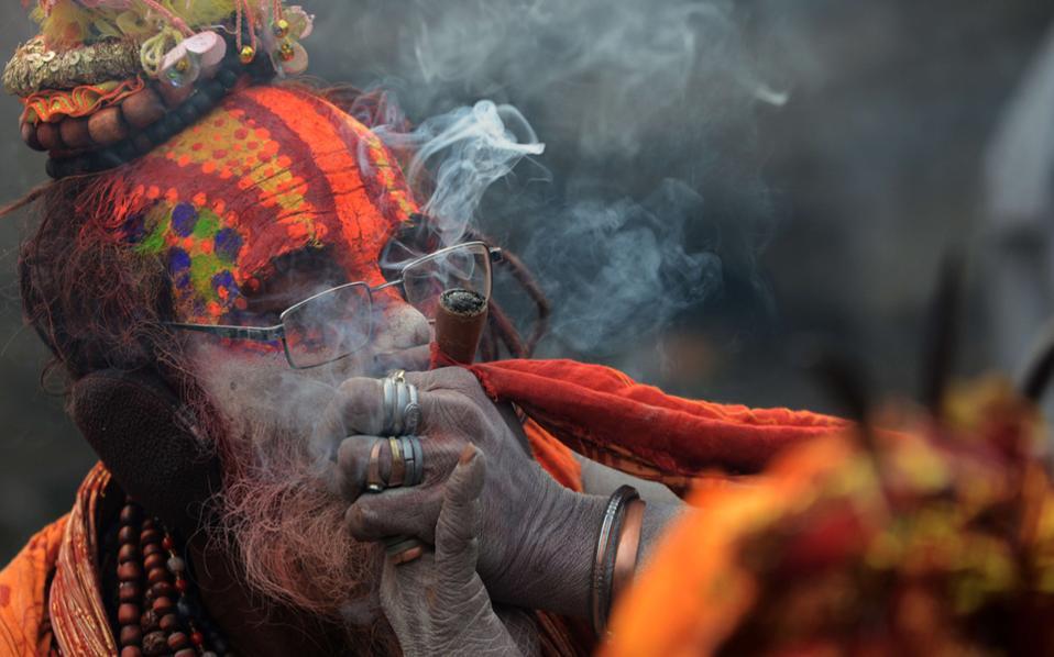 Καπνός, προσευχή και ιερό. Ιερή προσφορά στον θεό Shiva, ινδική θεότητα της δημιουργίας και της καταστροφής, το κάπνισμα μαριχουάνας από τους πνευματικούς του Νεπάλ στα πλαίσια του φεστιβάλ Kathmandu. AFP PHOTO / PRAKASH MATHEMA