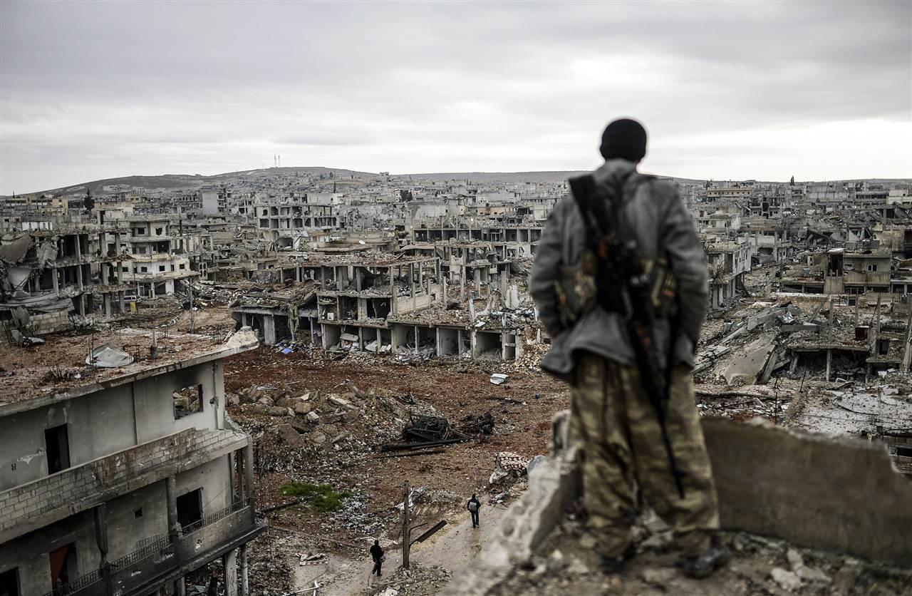 Κούρδος σκοπευτής κοιτάζει τα ερείπια της πόλης Κομπάνι, στα σύνορα της Συρίας με την Τουρκία. Στα χέρια των Κούρδων πέρασε πλέον ο έλεγχος της πόλης, μετά από πολύμηνες μάχες.