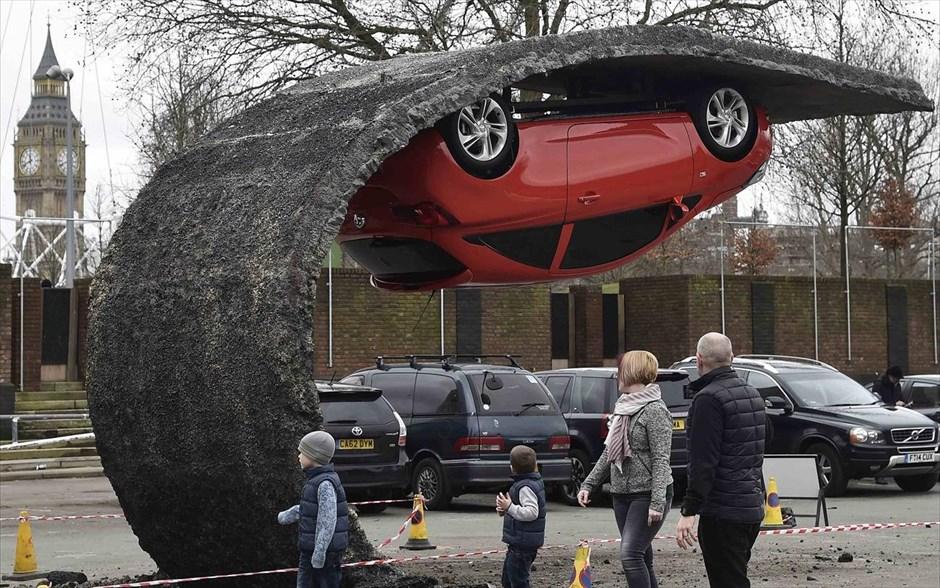 Αναποδογυρισμένο αυτοκίνητο σε έκθεση οχημάτων στο Λονδίνο. Το έργο έφτιαξε ο Βρετανός καλλιτέχνης Άλεξ Τσίμνεκ και φέρει τον τίτλο «Ανύψωσε τον εαυτό σου και συγκεντρώσου».