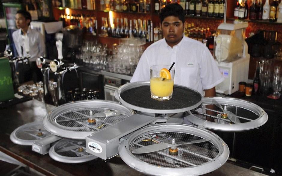 Η ρομποτική στην υπηρεσία τους σερβιρίσματος Πέμπτη, 05 Φεβρουαρίου 2015 13:17 Ένας μπάρμαν παρακολουθεί μία ιπτάμενη ρομποτική συσκευή σερβιρίσματος να απογειώνεται μεταφέροντας μία παραγγελία σε εστιατόριο της Σιγκαπούρης, κατά τη διάρκεια παρουσίασής της στα μέσα ενημέρωσης. Το μη επανδρωμένο όχημα αέρος (UAV), ένα μοντέλο που σχεδιάστηκε από την εταιρεία Infinium Robotics, έχει ως στόχο να «λύσει τα χέρια» των εργαζομένων στην εστίαση έτσι ώστε να ασχολούνται με «εργασίες υψηλότερης αξίας»