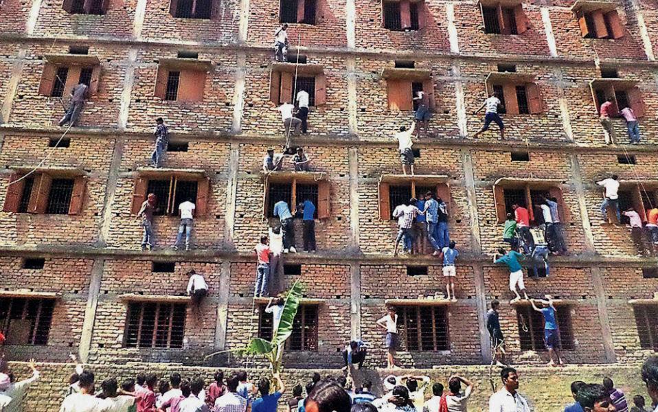 Σκονάκι. Στο εικονιζόμενο σιδερόφραχτο κτίριο διεξάγονται οι τελικές εξετάσεις του λυκείου στην πόλη Hijipur της Ινδίας. Αν απορείτε τι κάνουν σκαρφαλωμένοι και με κίνδυνο της ζωής τους οι κύριοι απέξω από το κτίριο,η απάντηση είναι εύκολη. Ότι θα έκανε κάθε γονιός που θέλει να προκόψει το παιδί του, να το υποστηρίξει και στην εσχάτη, να το βοηθήσει να γράψει. Σύμφωνα όμως με εκπαιδευτικές πηγές τουλάχιστον 600 μαθητές κόπηκαν από τις εξετάσεις γιατί έκαναν σκονάκι.... AP Photo/Press Trust of India