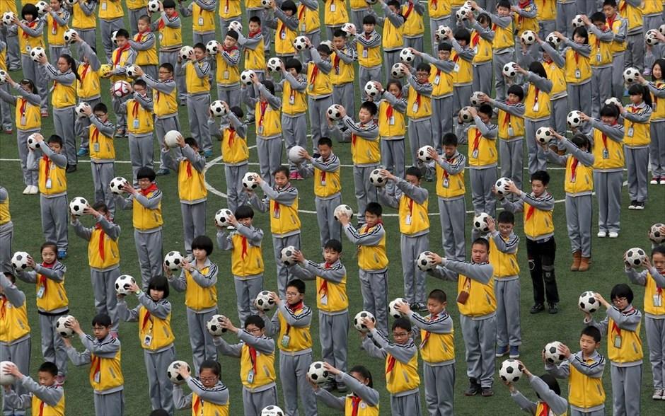 Μαθητές κάνουν πρωινές ασκήσεις με μπάλες ποδοσφαίρου, στην παιδική χαρά ενός δημοτικού σχολείου στο Λινχάι, στην επαρχία Ζετζιάνγκ.