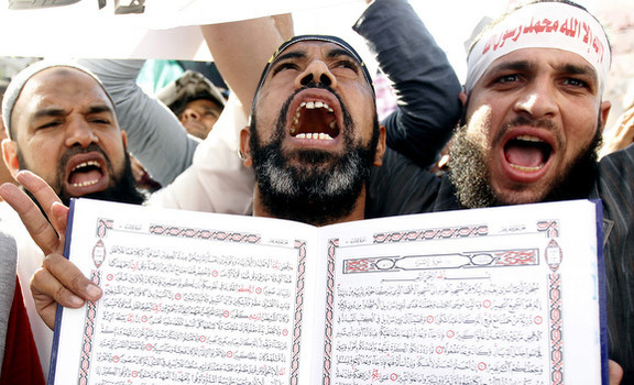 An Islamist Egyptian protester shouts holding a Koran during a protest of hundreds of Salafists gather for the enforcement of Islamic sharia law at Tahrir Square in Cairo