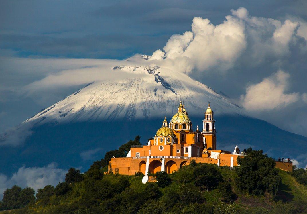 Το ενεργό ηφαίστειο Popocatepetl και η Μεξικάνικη Καθολική εκκλησία Iglesia de Nuestra Señora de los Remedios.