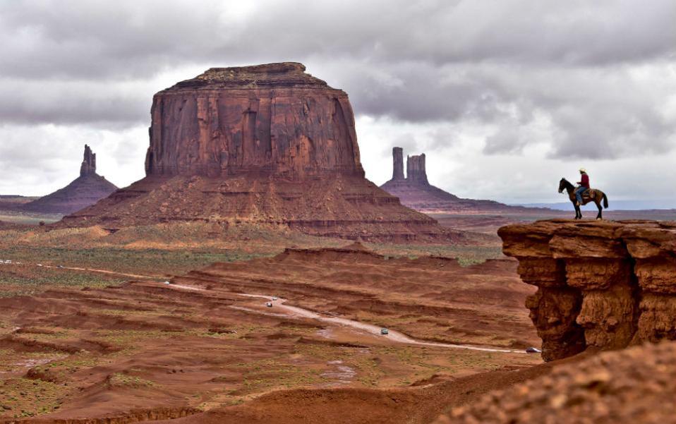 Την γη των Ναβάχο ατενίζει καβαλάρης ιθαγενής μπροστά από το Monument Valley Navajo Tribal Park της Γιούτα. Πριν θεωρήσετε ότι τίποτα δεν άλλαξε σε αυτή την γωνιά της Αμερικής, να σας πληροφορήσουμε ότι ο συγκεκριμένος ιθαγενής ποζάρει στον βράχο για να βγάλουν φωτογραφία οι τουρίστες. AFP PHOTO/MLADEN ANTONOV