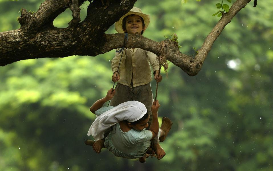 Ευτυχία. Το μόνο που χρειάζεται είναι ένα δένδρο, σχοινί και μια κουρελού για να κάθεσαι. Η κούνια είναι από τα αγαπημένα παιχνίδια των παιδιών. Ταχύτητα, λικνισμα και τα σύννεφα να έρχονται κοντά σου. Στην φωτογραφία δυο παιδιά παίζουν στο San Salvador. AFP PHOTO / MARVIN RECINOS