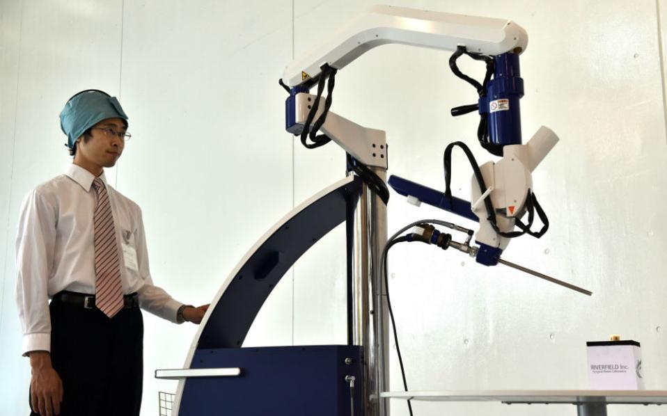 Μόνο για στοχοπροσηλωμένους γιατρούς!!! Ο μηχανικός της εταιρίας Rivenfield παρουσιάζει το πρώτο χειρουργικό ρομπότ που ελέγχεται από την σκέψη του γιατρού. Το Emaro θα χρησιμοποιείται για ελαφρές χειρουργικές επεμβάσεις και θα ελέγχεται από τον γυροσκοπικό αισθητήρα που βρίσκεται στο κεφάλι του γιατρού, μάλιστα θα πωλείται από τον επόμενο μήνα προς 125.000 δολάρια. AFP PHOTO / Yoshikazu TSUNO