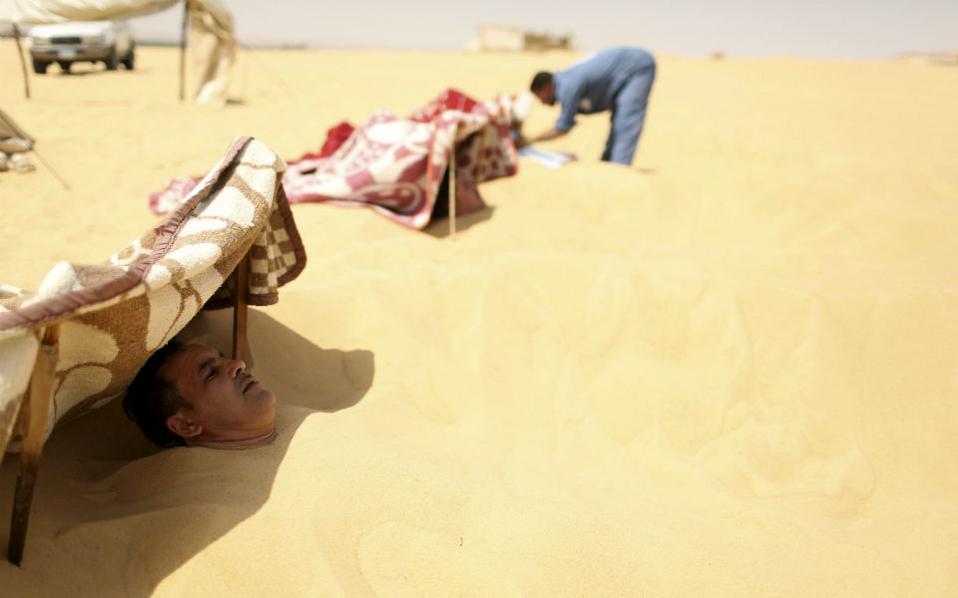 Η σάουνα της ερήμου. Την πιο καυτή ώρα της ημέρας διαλέγουν όσοι έχουν πόνους ρευματισμού και άλλες παθήσεις των οστών να επισκεφθούν τα θεραπευτικά αμμόλουτρα στην έρημο Σίβα. Οι ασθενείς ξεκουράζονται για λίγο στην σκιά και στην συνέχεια θάβονται μέχρι τον λαιμό από τους υπαλλήλους με καυτή άμμο ενώ παράλληλα τους κάνουν και μασάζ με τα πόδια τους. Μετά, καταϊδρωμένοι αλλά ανακουφισμένοι πίνουν το τσάι με μέντα που τους προσφέρουν στις πρόχειρες εγκαταστάσεις της ερήμου. REUTERS/Asmaa Waguih