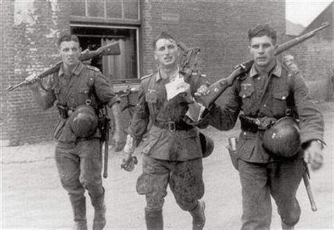 Three German soldiers returning from a recent fight 2